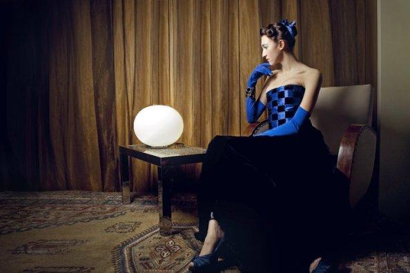 donna elegante seduta in poltrona che guarda la lampada bianca su un tavolino basso